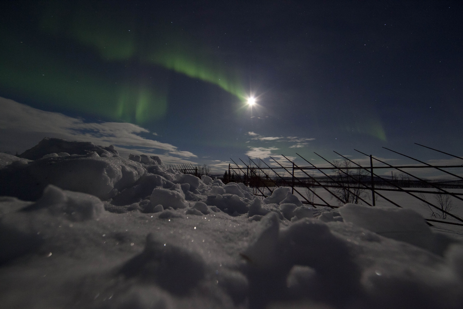 Northern lights over snow, moonlight in the background