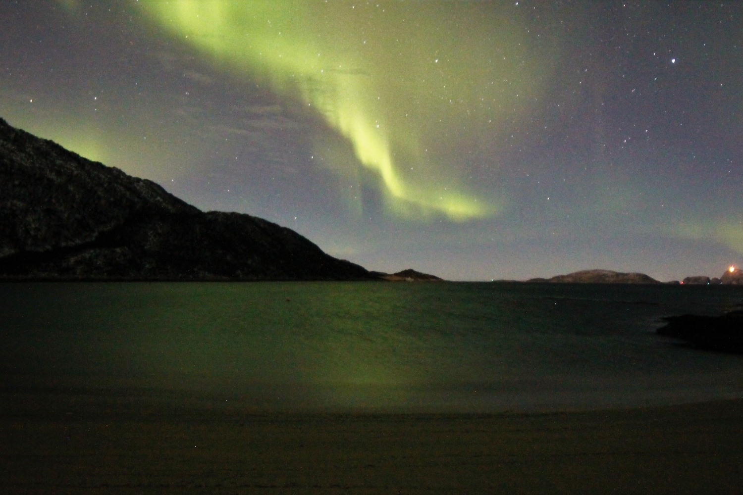Northern lights above dark mountains
