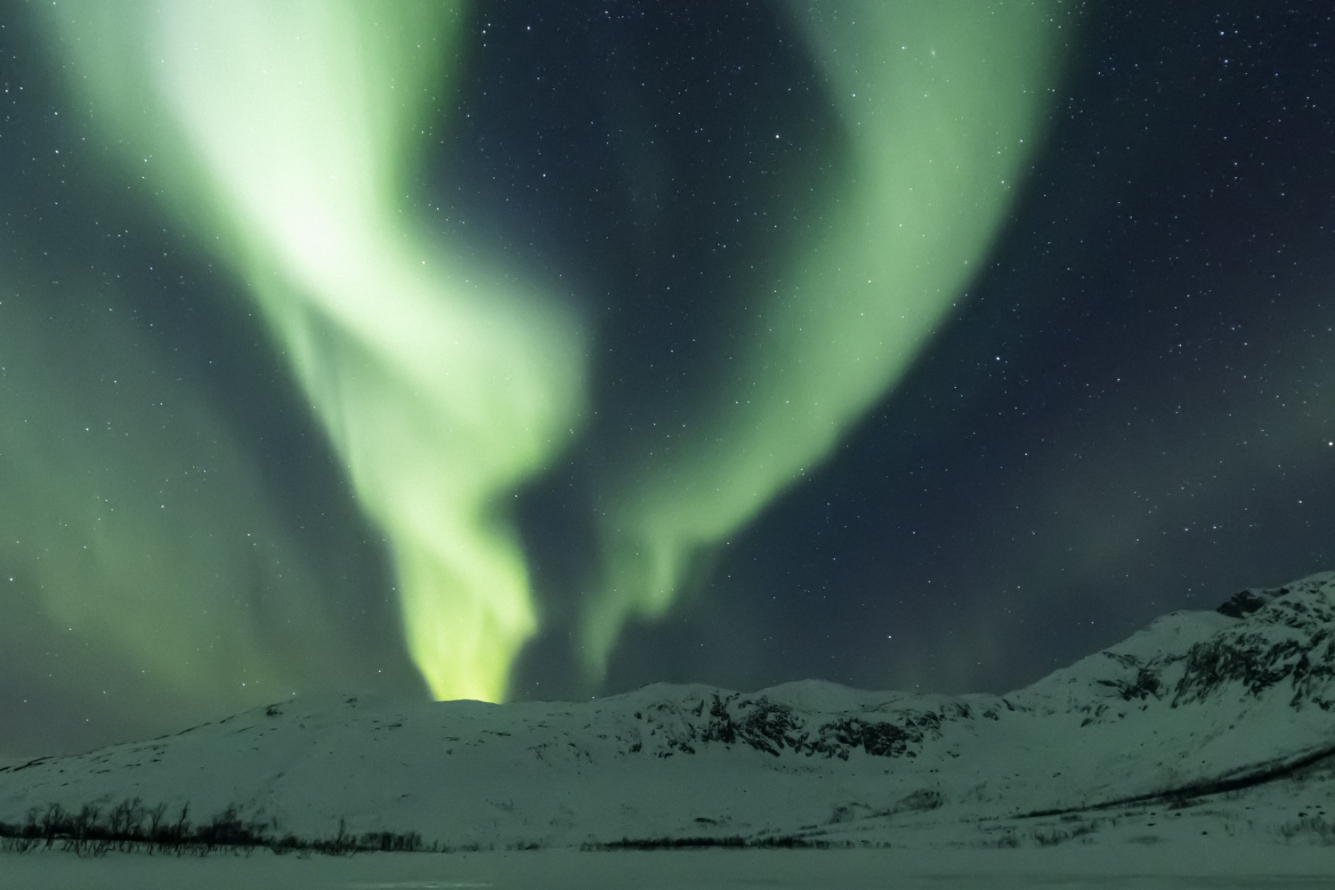 Northern lights above snowy mountain