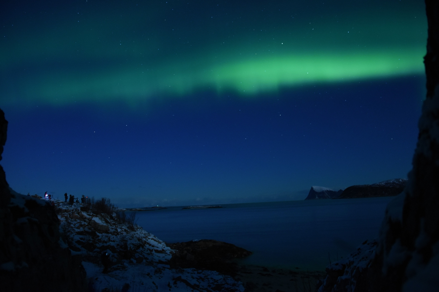 Northern lights above fjord and sea