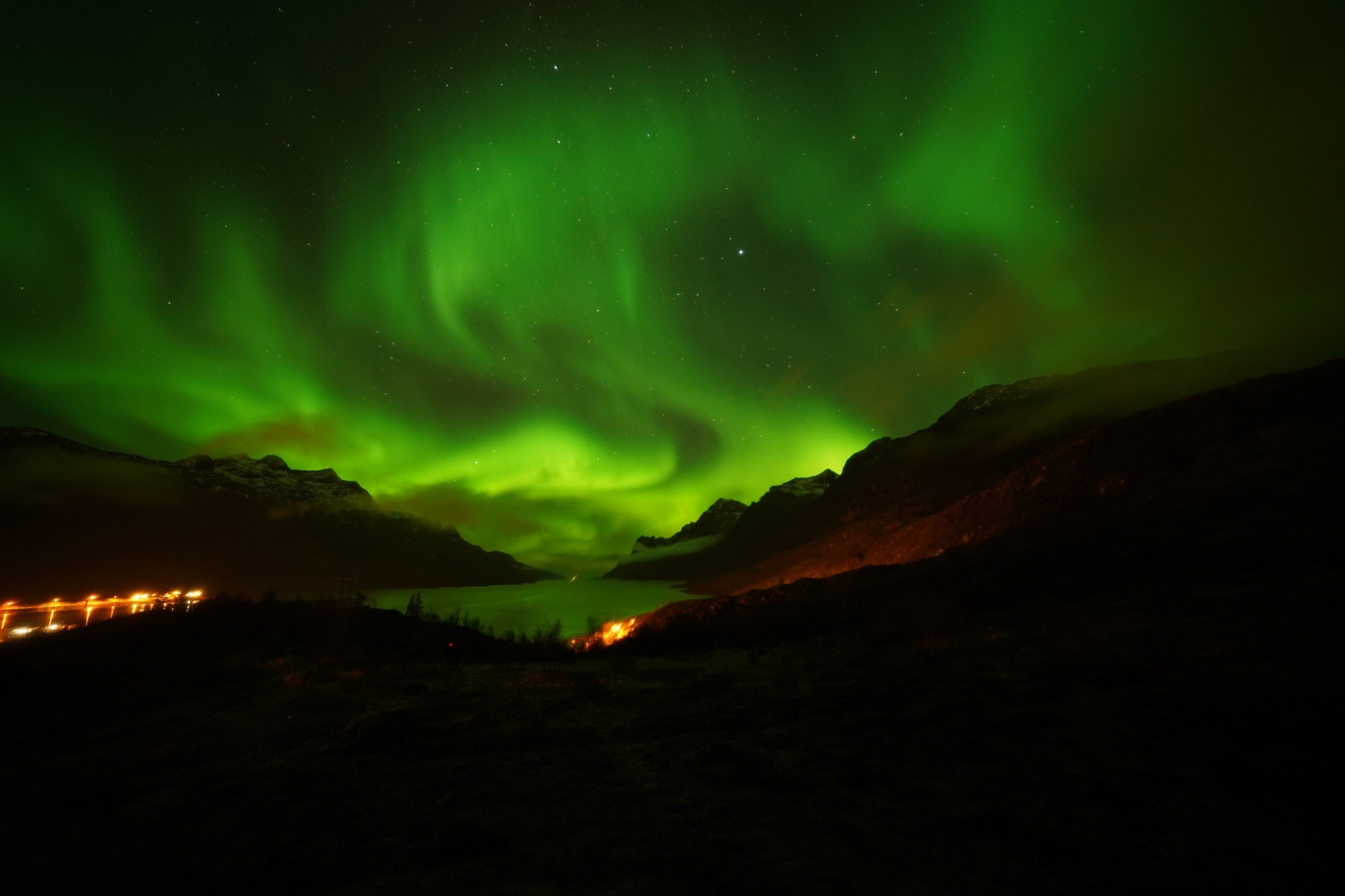 Northern Lights between mountains and fjord