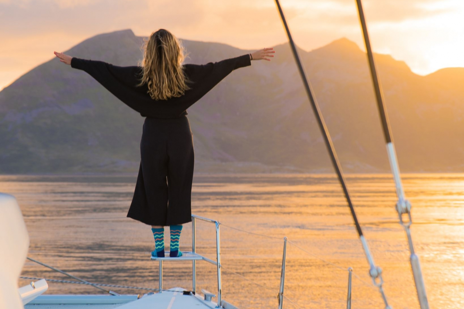 Lady in the front of the deck doing the Leonardo DiCaprio pose from Titanic with mountains and midnight sun in the background