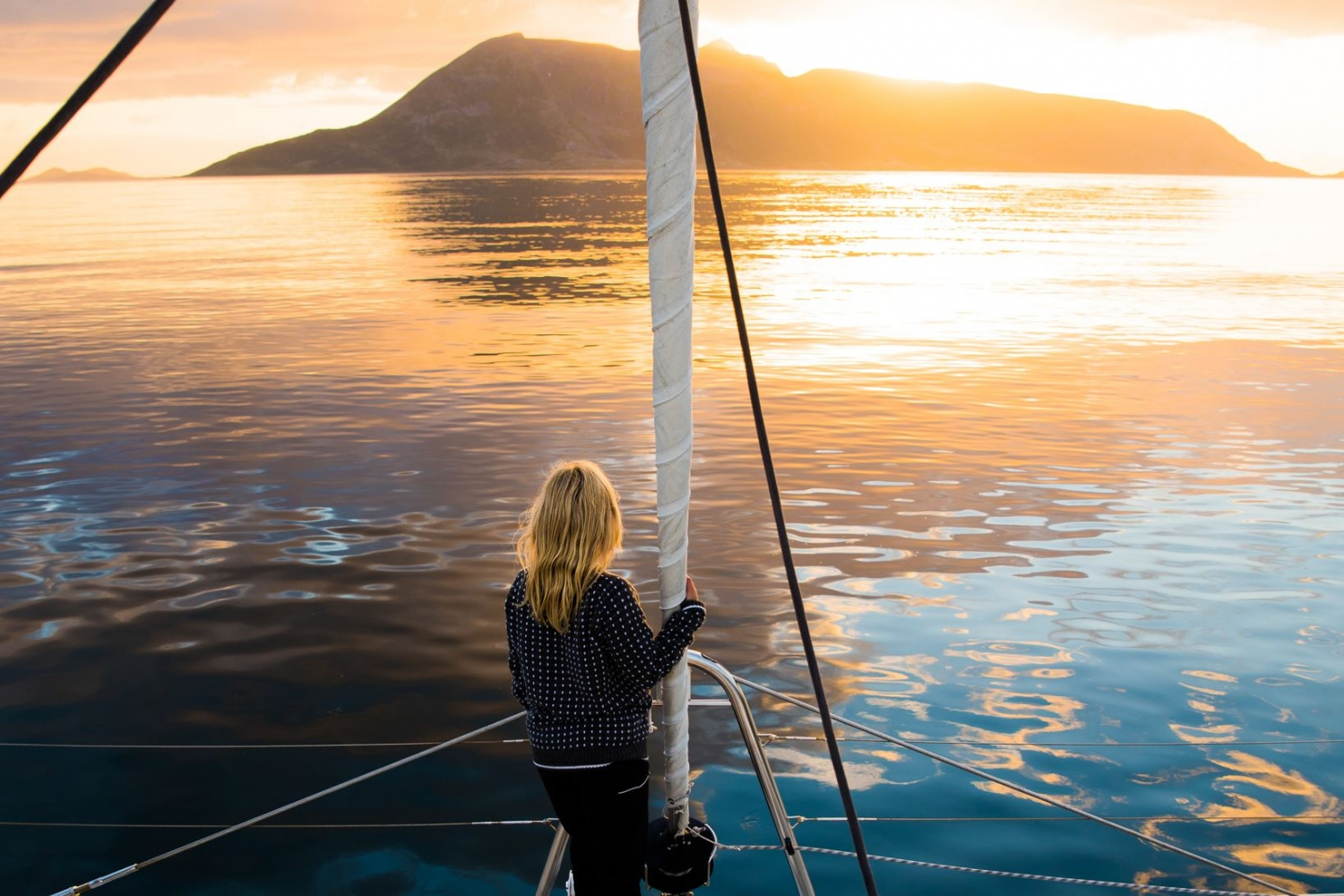 Lady watching the midnight sun, clear waters and  mountain