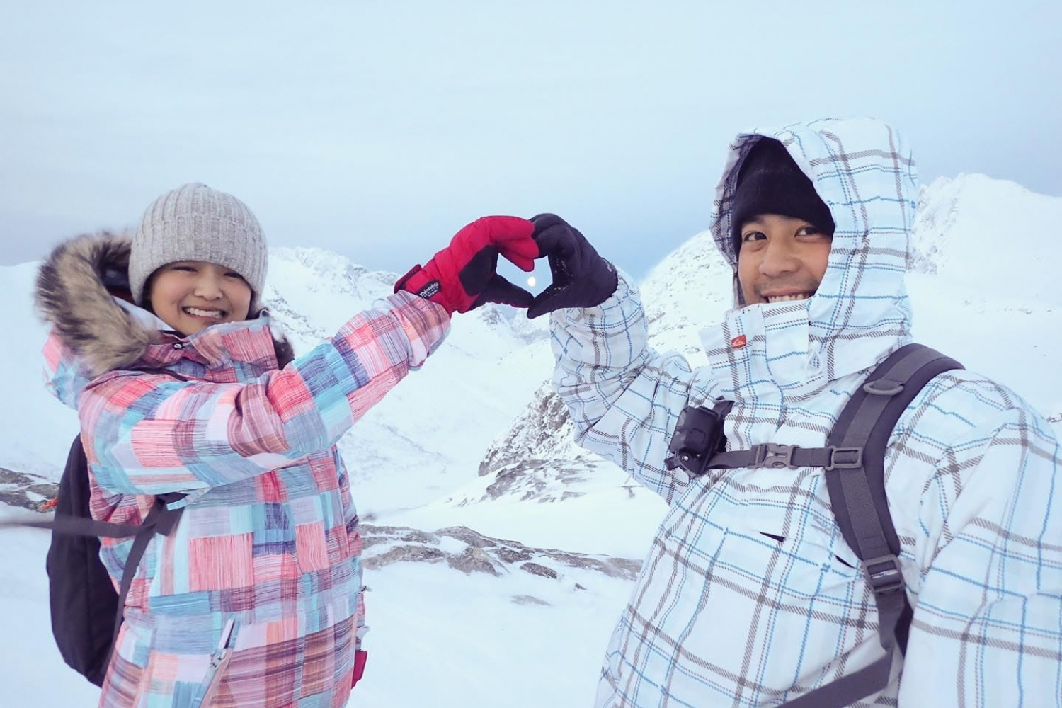 Couple making a heart with their hands, snowy landscape in the background