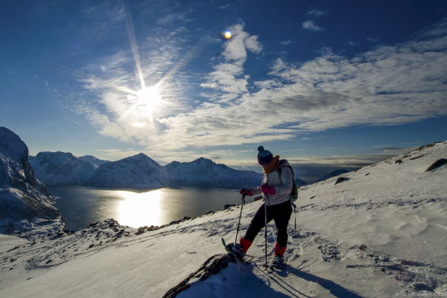 Person with snowshoes in a snowy mountain with sea, mountains and the sun in thebackground