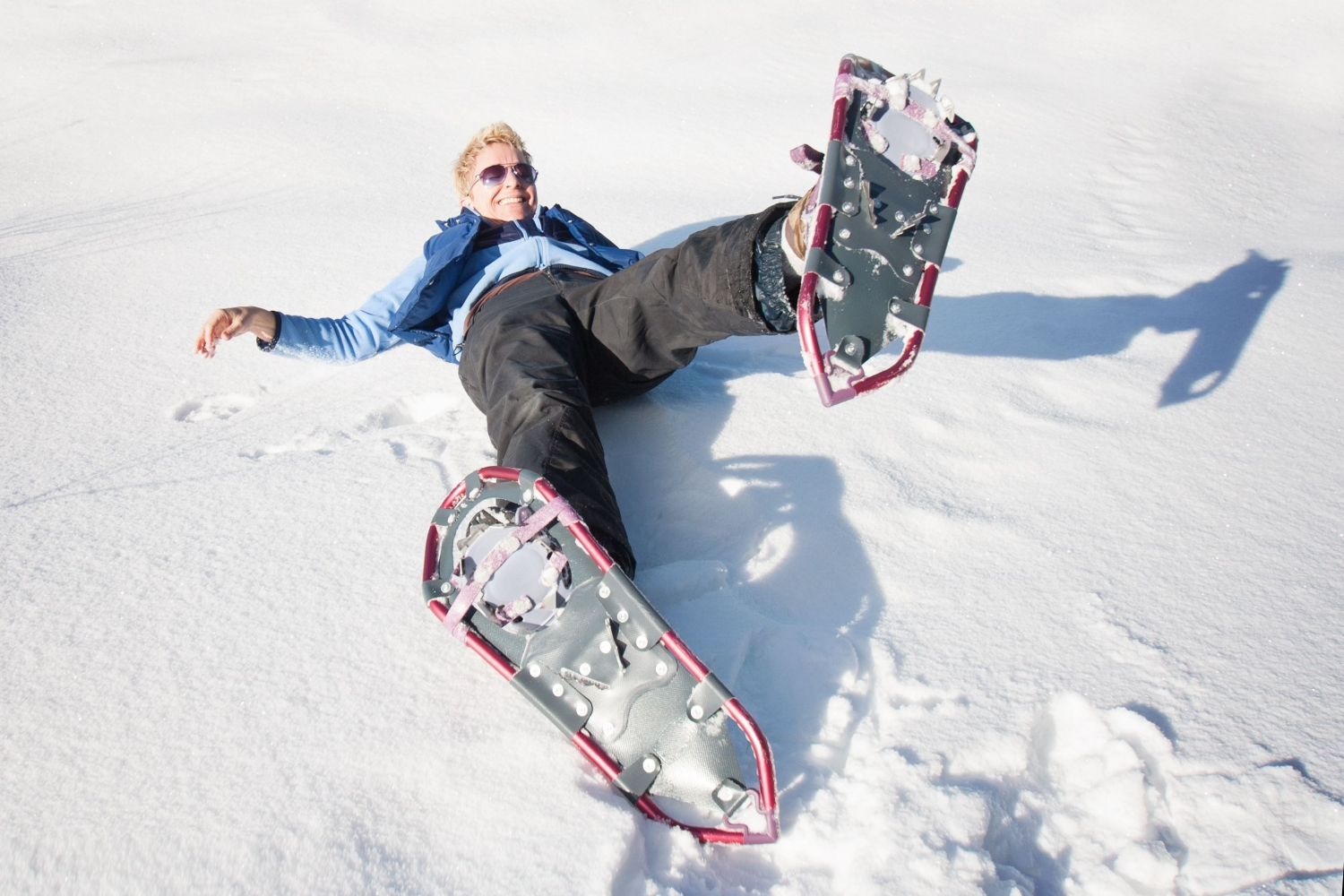 Person fallen down on the snow wearing snowshoes