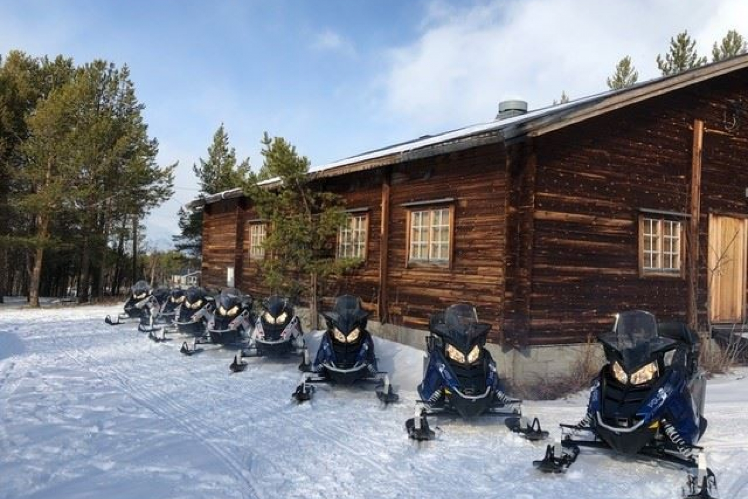 snowmobiles in front of a cabin