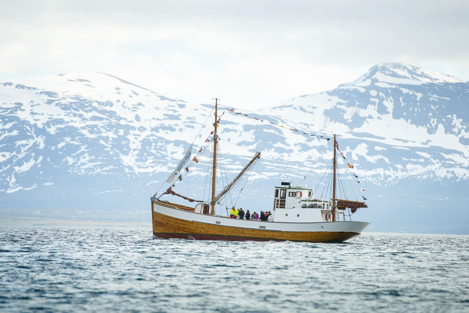 The wooden boat Hermes II out on the sea with snowy mountains in the background