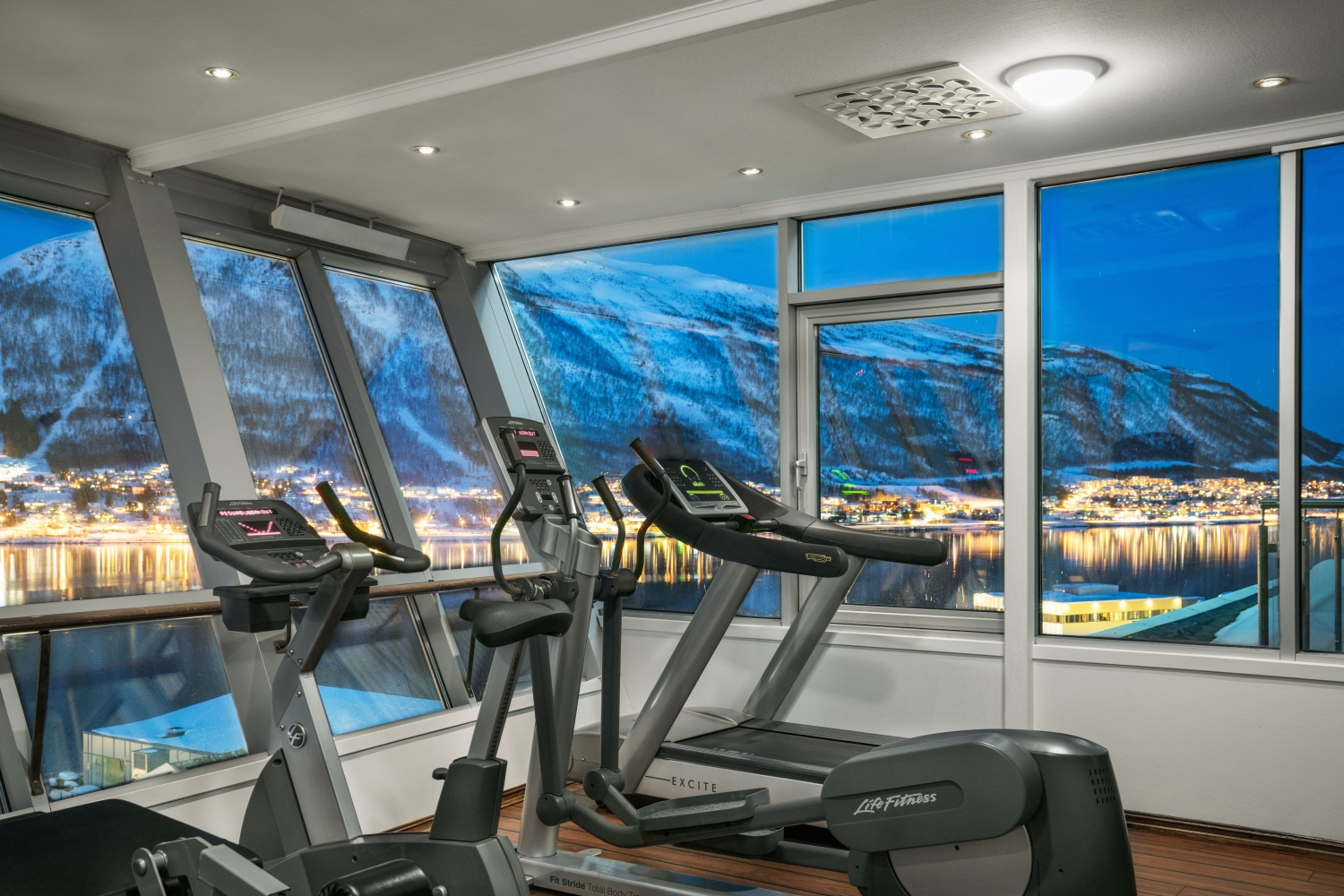 a gym with treadmils and an amazing view