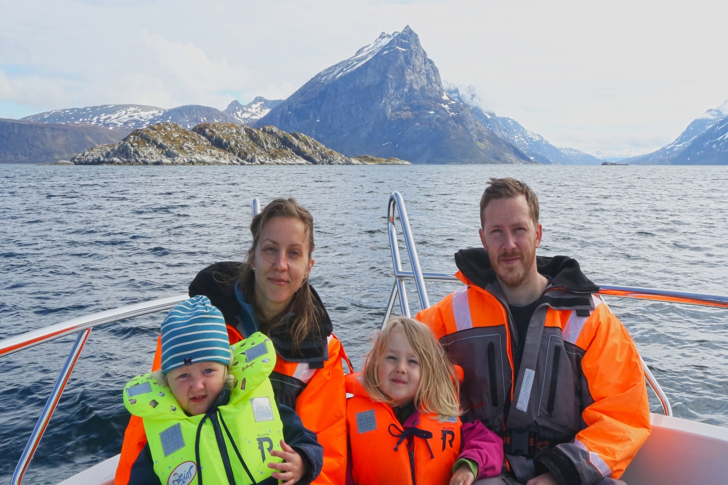 A family sitting on the boat, sea and mountain in the background