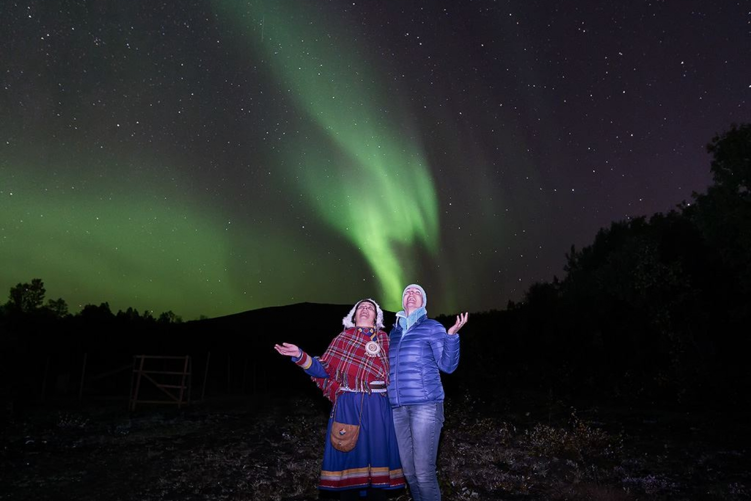 Sami lady and guest admiring the Northern lights together