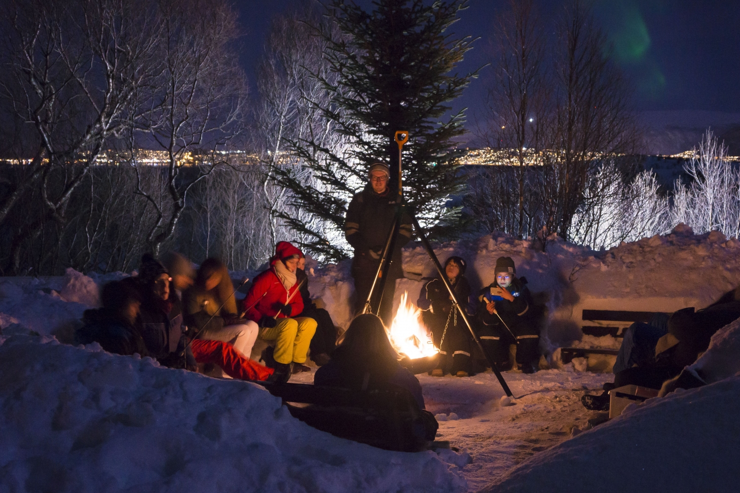 Guests gathered around the bonfire in snowy landscape