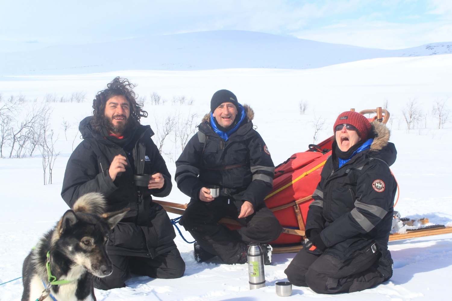 Three mushers resting next to a sled