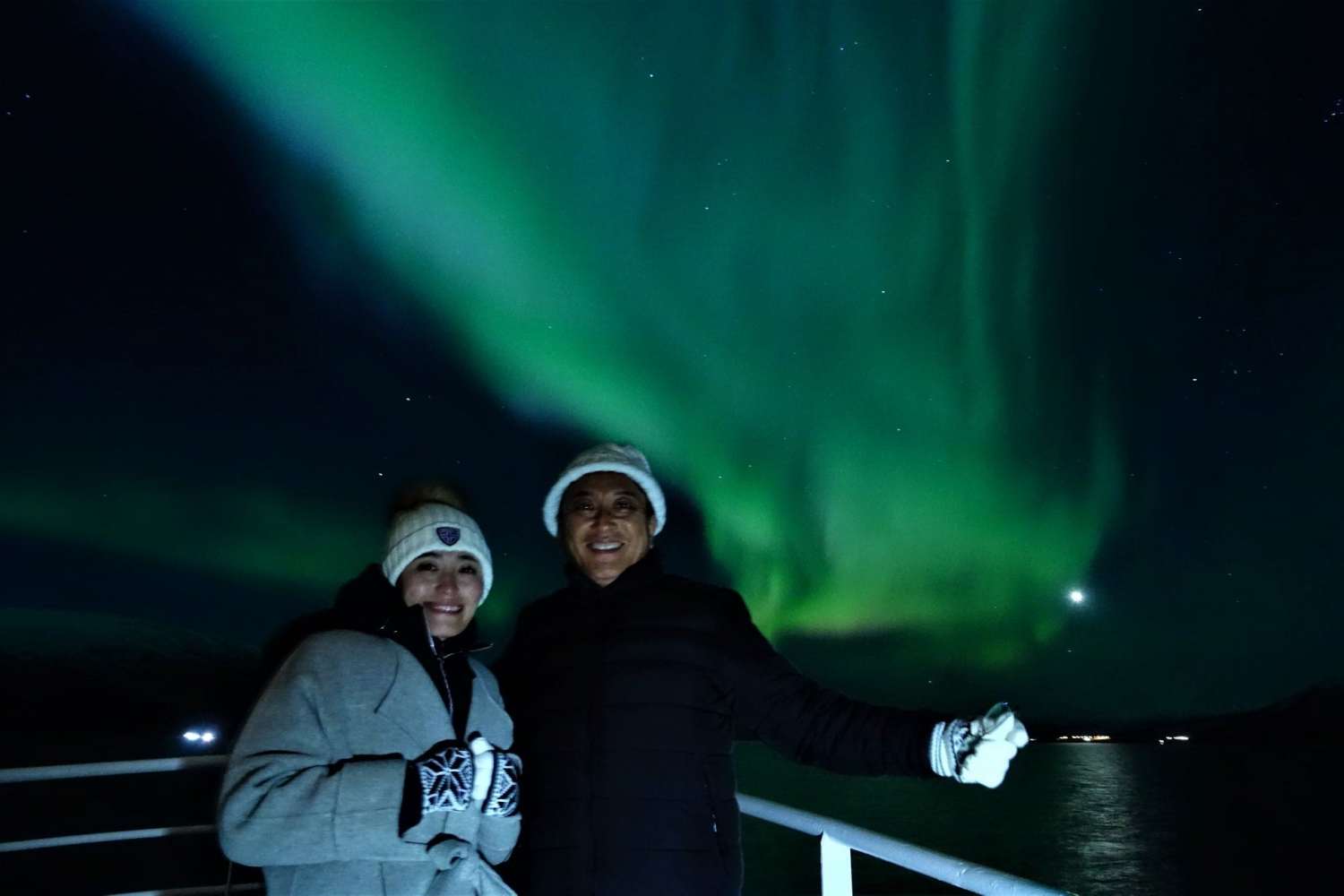 Two persons smiling with The Northern Lights in the background