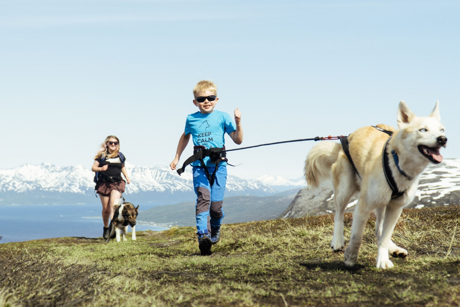Woman and child running with huskies on top of the mountain