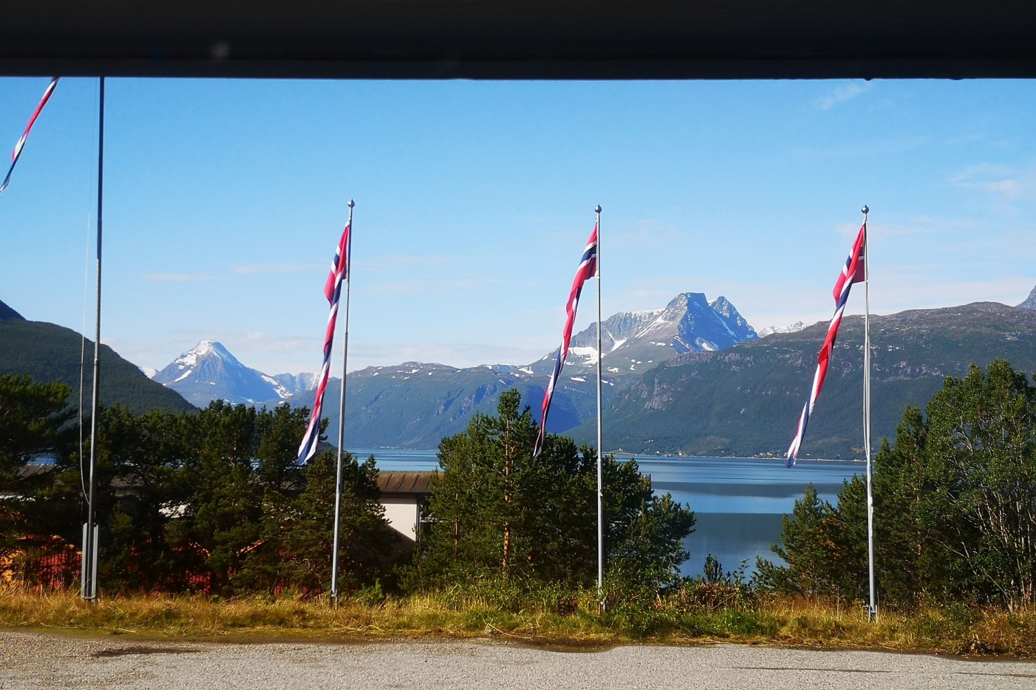 Norwegian flags, in the background a view over sea and mountains